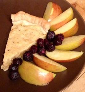 Cheese pie served with fresh apple slices and blueberries